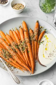 Sweet roasted whole carrots are sprinkled with a crunchy, seedy pistachio dukkah and served with a cool dollop of tahini yogurt sauce.