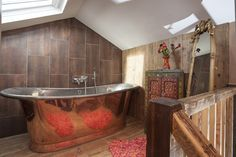 A copper bath tub brings bronze and bright colours into the bathroom