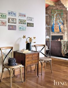 The sitting room of one son's suite can be glimpsed from its entry, which is personalized with his collection of vintage license plates. A table and chairs setting from Maze Home in Winnetka, Illinois, sits in repose. Arizonabased artist Matthew Sievers' oil on canvas hangs above the fireplace beyond.