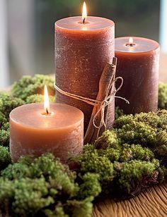 O conjunto de três velas, uma de cada altura, pode decorar um aparador. O musgo dá o charme