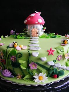 I love the adorable little mushroom house decorating the top of this cake