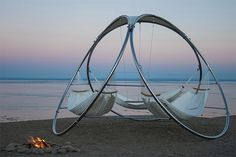 Triple Hammock from Trinity Hammocks. A stainless steel tubular structure suspends three hammocks and a small teak table in the center.