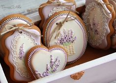 Delicate Lilac Flowers Royal Icing Design On Sugar Cookies Adorned with Hole and Ribbon.