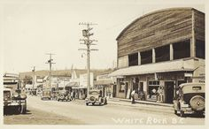 https://flic.kr/p/E1o5o6 | c. 1933 Postcard View - White Rock, B.C. Waterfront area showing the Feedham's Block (Mini Reno!) | The shopkeepers in the Feedham Block were realtor George Thrift (the sign on the postcard reads - Geo. M. THRIFT / REAL ESTATE) - Next was a Barber Shop (Dick Thompson) and the BLUE MOON / CAFE and Confectionery Store (sign reads - Confectionery / Drug Sundries / Tobaccos / Ice Cream / Ice Cold Drinks) There is also a folding sign on the sidewalk area - Westminster…