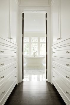 Long, narrow walk through closet features floor to ceiling built-in cabinets atop dark stained oak wood floors.