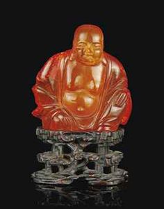 A CHINESE AMBER CARVING OF BUDAI - 19th century -The figure carved seated with loose robes revealing the bare chest underneath, the face with serene expression and pendulous ears