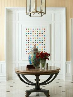 Loving the juxtaposition of fun, colorful artwork with a more traditional table and tablescape.