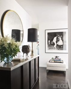 In the entry, a console by Calvin Klein Home holds a vintage lamp and a brass vessel, the mirror is by Restoration Hardware, and the photograph is by Malick Sidibé.