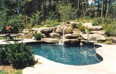 A dramatic hillside rockery with waterfall extends down into the pool to help create a Muskoka feeling for this black pool. The natural stone coping and deck define entertaining areas extending on either side. (13 x 20 Custom Freeform)