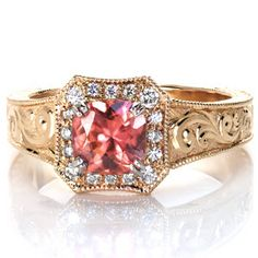A uniquely shaped halo is bead-set with vibrant diamonds. The wide ring is detailed with gorgeous hand engraved designs and hand formed filigree curls.