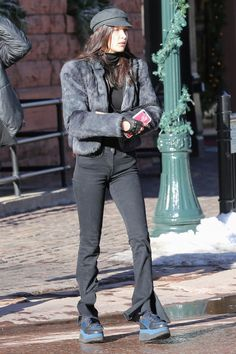 Bella Hadid wearing 3x1 W2 Split Seam Bell Jeans in Black Stone, Wildflower Ciao Bella Iphone Case, Isabel Marant Etoile Evie Hat and Louis Vuitton Palm Springs Mini Backpack