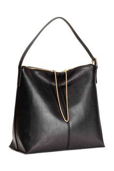 Handtas: Een handtas van generfd imitatieleer met een verstelbare, gewatteerde schouderriem en een ritssluiting met een decoratief metalen kettinkje. De tas heeft drie binnenvakken waarvan één met rits. Gevoerd. Afmetingen 14x31x33 cm.