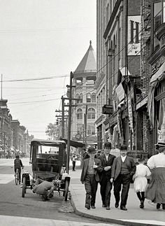 STREET SCENE: Circa 1908 - High Street Holyoke Massachusetts. Looks as though a man is having problems with his car.