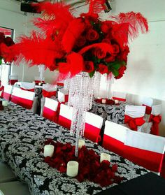 Batz Mitzvah centerpiece of red roses and red ostrich feathers atop crystal chandelier with rose petals and candles at base.  Doristhefloristt@aol.com