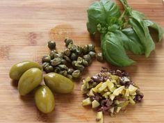 INVOLTINI DI POLLO CON OLIVE E CAPPERI 2/5 - Snocciolate le olive e tagliatele a pezzetti, staccate le foglie del basilico e lavatele. Dividete i pomodori a cubetti eliminando i semi.