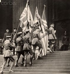 Flags which signal America's entrance into WWI are carried up stairs in London.