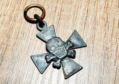 Krzyż Huzarów Śmierci 1920 r. -DYONU HUZARÓW ŚMIERCI, unikatowy, w wersji wojennej, frontowej, jeszcze bez mieczy - pierwowzór późniejszego z 1921 r. Krzyż żelazny, czaszka lutowana do ramion krzyża. Wszystkie wersje emaliowane z mieczami, to produkt powojenny - pierwsze egzemplarze wykonano w 1921 roku. Ten powstał w trakcie działań wojennych dla elitarnego oddziału - DYONU HUZARÓW ŚMIERCI, i stał się pierwowzorem późniejszej odznaki.