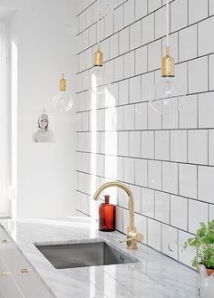 White kitchen with marble countertop and ceramic tile backsplash. Pretty gold pendant lights.