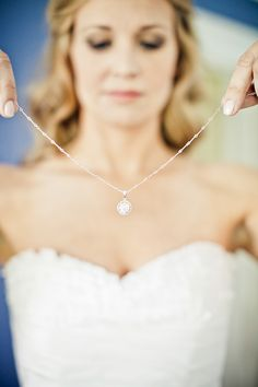 Thr bride putting on her gorgeous sparkly necklace, photos by JAG Studios | via junebugweddings.com