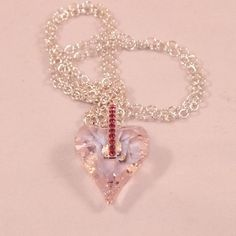 Here is a gorgeous, sparkling, heart shaped pendant in pale pink rosaline Swarovski crystal teamed up with sterling silver.I made the pendant by attaching a sterling silver bail encrusted with pink CZ crystals to a 27mm Swarovski crystal pink rosaline heart. I then threaded it on to a fine sterling silver curb chain. The photos don't do the heart justice as it is such a pale pink it is hard to photograph. I have hung the pendant on a sterling silver chain that measures 23