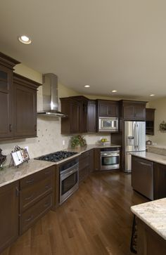 Hardwood flooring. Stained cabinetry with decorative hardware and crown molding. Diamond lay tile above cooktop over square tile deco backsplash. Stainless steel appliances with brushed nickel faucet. Two level granite countertop island. Recessed lighting with small pendants over island.