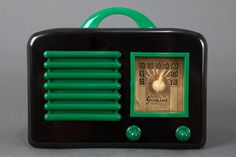"""Beautiful General Television radio made of glossy jet black Bakelite, with beautifully contrasting kelly green handle, grill, knobs, and dial face frame. Made in mid 1940's by General Television Radio Corp of Chicago, Illinois, model """"5E5"""". The gold face features a stunning textured deco sunburst pattern, with a yellow plastic station indicator, beneath which """"General Television"""" appears."""