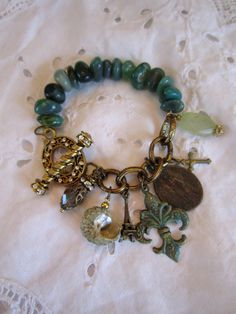 vintage repurposed jewelry religious charm bracelet eiffel tower fleur de lis shell aquamarine medal rhinestone toggle atelier paris on etsy. $86.00, via Etsy.