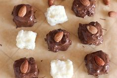 1/4 cup raw almonds 3 tablespoons corn syrup 1 1/2 cups powdered sugar 1 tablespoon melted butter 2 cups shredded coconut 1/2 teaspoon coconut extract (optional) 1/2 teaspoon vanilla extract 1 1/2 cups milk chocolate