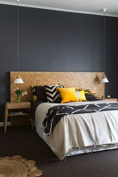 bedroom with charcoal grey wall paired with warm earthy tones, yellow accents and hanging pendant lights in place of bedside lamps (styling by Ruth Welsby, photography by Martina Gemmola - via Inside Out magazine)