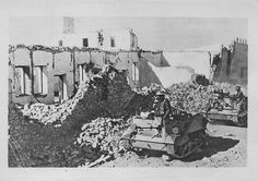 Text says Fort Capuzzo.    Fort Capuzzo was a Fort in the Italian colony of Italian Libya, located near the Libyan-Egyptian border. It changed hands between the Allies and German/Italian forces several times over the course of the war.   As far as I can tell these are Allied troops in Universal Carriers (also called Bren Carriers)