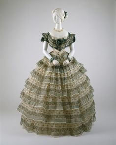 An 1855 evening ensemble with an elaborate 7-layer flounced skirt decorated with flowers and stripes. The introduction of the cage crinoline in the 1850s allowed skirts to reach enormous sizes. It also saw a vogue for horizontal stripes which echoed the structure of the new crinolines.