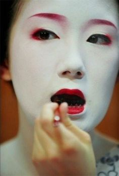 This is a maiko (apprentice geisha) blackening her teeth for her debut as a geiko (geisha). During the heian era, this practice was done for cosmetic and health reasons. The teeth were more protected from decay, and it was more beautiful than having yellowing teeth with white face powder.  Geisha continue the practice for special ceremonies if they wish.