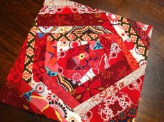 """Scrappy red rosette that I made yesterday (part of my """"red sticks"""" inspired quilt that's in progress)."""