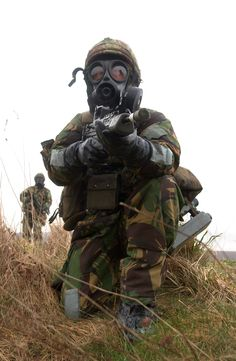 A British soldier wearing full Individual Protective Equipment (IPE) is pictured aiming his SA80 riffle during a chemical defence exercise at the Defence NBC Centre Winterbourne Gunner Barracks Feb 2003. [3000  4594]