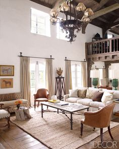Reese Witherspoon's Ojai Home - Living Room :: The 19th-century leather chairs in the living room are English, the sofa is by Buckingham, and the settee is upholstered in a Rogers & Goffigon velvet; the small table is made from an apple-tree stump, the curtains are of a cotton from Claremont, and the jute rug is by Pottery Barn.