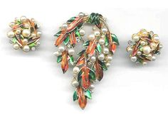"Autumn Leaves Set:  Warm and glowing, the enameled leaves of this brooch and clip earring set are full of life.  Simulated pearls resemble berries or perhaps dew drops interspersed among the leaves.  Exceptional condition.  Marked: ART ©   Brooch: 2½ by 1¾""; Earrings: 1"" diam 