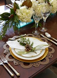 beautiful jute placemat, evergreens, pinecones and neutral flowers