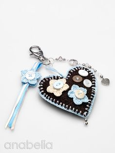 A beautiful collection of crochet edged fabric heart key chains embellished with buttons, and crochet flowers by Anabelia