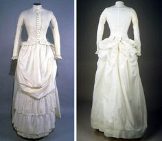 Dress, ca. 1886-88. Ivory cotton eyelet.  Bodice opens center front & fastens w/17 mother of pearl buttons flanked by vertical tucks. Overlaid is ivory cotton w/whitework,  embroidered eyelet, & scalloped edge. High round neckline w/short standing collar. Skirt has large swag across front, 2-layer eyelet ruffle, & pleated hem. Back is very full in bustle area. Cotton tapes attached to inside in order to kirtle bustle area into large puffs. Museum of American Textile History
