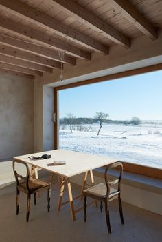 """Minimalist interiors with bare rafters, integrated furniture and mottled walls place emphasis on the views out through the large sliding windows. The architects used these large expanses of glazing with the aim of giving each room the feeling of a """"niche-like shelter in the open space of the landscape""""."""