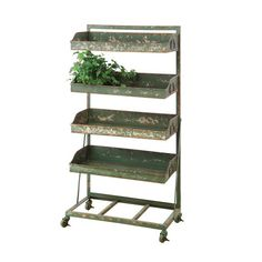 In your home, this sweetly distressed green metal shelf holds up your favorite decor and memorabilia with rustic charm. The sturdy frame stands on a wheeled base, so it's well adapted to moving around the kitchen. It would also work wonders outdoors for sorting out plant starts and garden equipment.