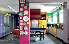 A moradora é apaixonada por cores e não teve medo de ousar na cozinha. Além dos tons fortes, ela decorou o ambiente com quadros e pratos pendurados nas paredes