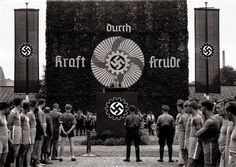 "An event promoting the 'Krat Durch Freude' (""Strength Through Joy"") program, instituted as part of the National Socialist platform. The program sought to bridge the gap between the lower and middle classes by offering state-subsidized leisure activities and commodities. Some of these for example include tickets to concerts, day trips to resorts, or even entire vacations to Fascist Italy. The Krat Durch Freude organization was also credited for the inception of the Volkswagen, originally…"