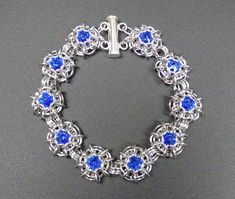 You will receive the exact bracelet shown in the pictures. This Phaedra bracelet designed by Karen Synder is handcrafted link by link out of aluminum, and Swarovski sapphire rivolis. Chainmaille is a wonderfully tactile medium with its own unique flow and movement. Approximately