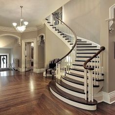 Foyer with curved staircase in white and dark hardwood and crown moldings. Description from pinterest.com. I searched for this on bing.com/images Love this!