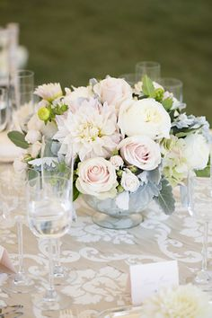 Table top:  Low mercury bowls of lush overflowing arrangements composed of pale blush and grey – antique hydrangea, Sahara rose, Café au Lait Dahlias, Patience Garden roses, Champagne Lisianthus, Dusty Miller, and vines