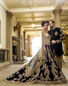 Bridal in long tail dark blue lehnga choli and groom in matching short sherwani with golden pajama latest indian and pakistani wedding matching dress combinations for bride and groom 2017