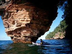 A Lake Superior kayaker maneuvers past sea caves that pock the Apostle Islands.