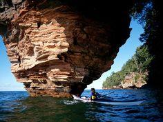 A Lake Superior kayaker maneuvers past sea caves that pock the Apostle Islands.