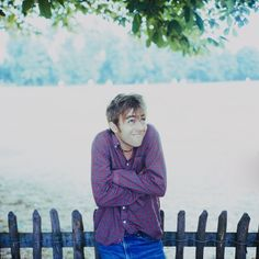 Damon Albarn in front of fence